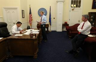 Nevada Gov. Brian Sandoval signs bills in his office at the Capitol with intergovernmental affairs manager Tyler Klimas, center, and Chief of Staff Gerald Gardner during the final hours of the 77th legislative session in Carson City, Monday, June 3, 2013.