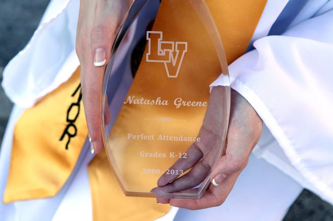 Las Vegas High School valedictorian Natasha Greene shows off her perfect attendance plaque during her commencement ceremony on the school's football field in Las Vegas on Friday, June 7, 2013. Greene has had perfect attendance and perfect grades since kindergarten.