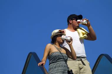 A couple keeps hydrated while visiting the Las Vegas Strip Sunday, June 9, 2013. Sunday's high temperature was 109, two degrees shy of the record.