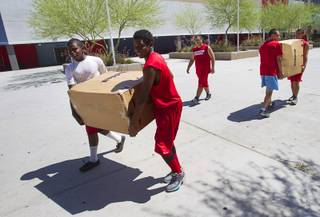 Football players carry boxes of new equipment into Western High School Monday, June 10, 2013. The high school football programs at Chaparral and Western received donations of $500,000 to upgrade everything from the weight room to field equipment and new uniforms.