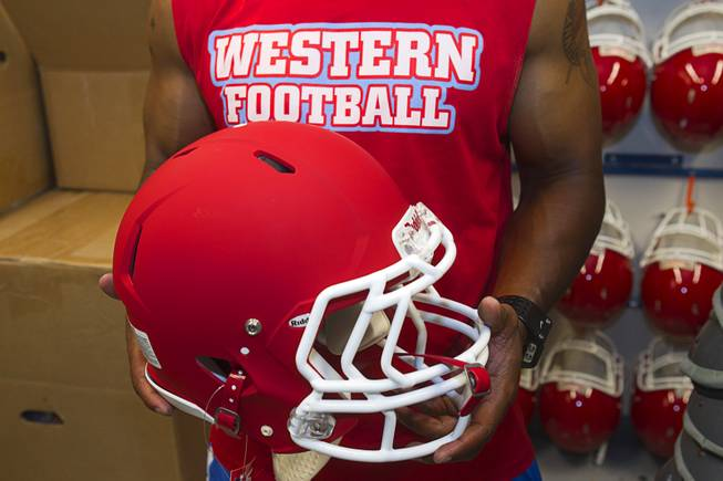 Western High School football coach Donnie Davis holds a new helmet at the school Monday, June 10, 2013. The high school football programs at Chaparral and Western received donations of $500,000 to upgrade everything from the weight room to field equipment and new uniforms.