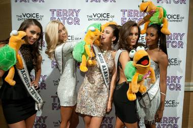 Miss USA contestants play with Winston the Turtle puppets prior to the Terry Fator: The Voice of Entertainment show at the Mirage in Las Vegas, Nevada on Monday, June 10, 2013.