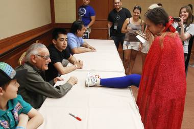 Veronica Fink reacts as she puts her foot on the table to have comic legend Stan Lee sign her shoe at the Amazing Las Vegas Comic Con at the South Point Saturday, June 15, 2013.