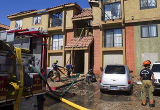 Firefighters pull hose after putting out a three-alarm apartment fire at 28th Street and Cedar Avenue Sunday, June 16, 2013. Two people suffered minor injuries, Las Vegas Fire & Rescue spokesman Tim Szymanski said.
