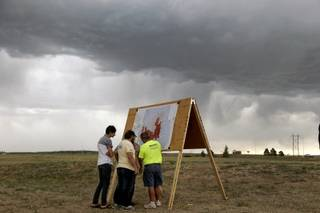 Residents look at a map detailing the progress of the Black Forest wildfire Sunday, June 16, 2013, in Colorado Springs, Colo. Fire crews were putting out hot spots Sunday to prevent flare ups in heavily wooded Black Forest, where hundreds of houses have been destroyed.