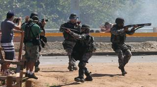 Riot police aim their weapons at protesters gathering near the Castelao stadium in Fortaleza, Brazil, Wednesday, June 19, 2013. Protesters cut off the main access road to the stadium where Brazil will play Mexico in the Confederations Cup soccer tournament later Wednesday. Beginning as protests against bus fare hikes, the demonstrations have quickly ballooned to include broad middle-class outrage over the failure of governments to provide basic services and ensure public safety. (AP Photo/Andre Penner)