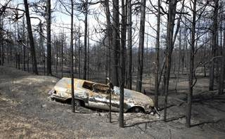 A burned automobile sits off the roadside in the burned forest on the Black Forest wildfire north of Colorado Springs, Colo., on Monday, June 17, 2013. Over 470 homes burned in the wildfire that started last Tuesday.