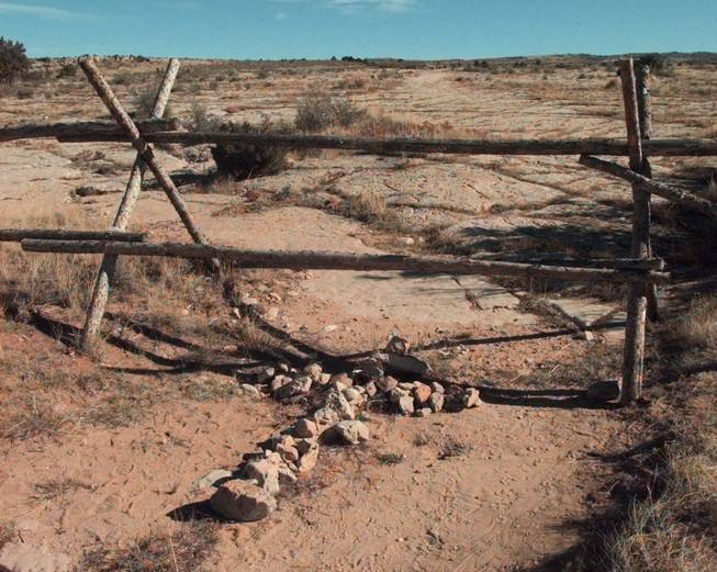 In this Saturday, Oct. 9, 1999 file photo, a cross made of stones rests below the fence in Laramie, Wyo. where a year earlier, gay University of Wyoming student Matthew Shepard was tied and pistol whipped into a coma. He later died. The killers, police said, targeted him because he was gay. Congress passed anti-hate crimes legislation bearing his name in 2009.