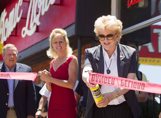 Las Vegas Mayor Carolyn Goodman, right, uses a torch to cut a tape during the grand reopening of The Atomic on East Fremont Street Wednesday, June 20, 2013. Looking on are Allan Palmer, left, CEO/executive director of the National Atomic Testing Museum, and Jennifer Albright. The bar was was originally built in 1945 as Virginia's Cafe but was renamed Atomic Liquors in 1952 when patrons used to go to the roof to watch the nuclear blasts from the Atomic Test Site.