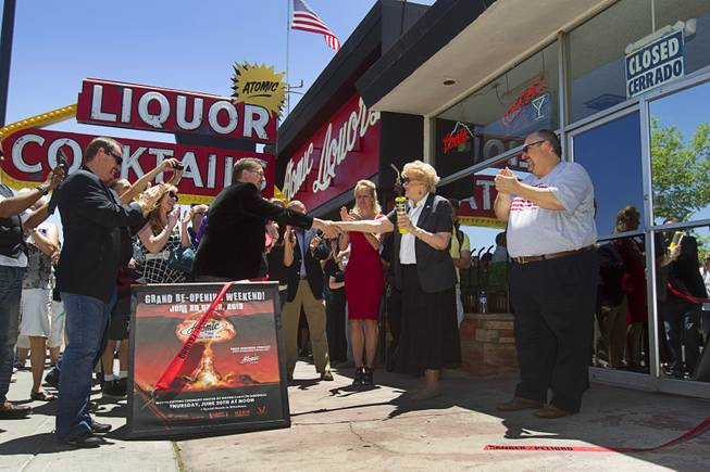 Las Vegas Mayor Carolyn Goodman shakes hands with Atomic co-owner Derek Stonebarger during the grand reopening of The Atomic on East Fremont Street Wednesday, June 20, 2013. The other owners are Lance Johns, left, and his brother Kent, right. The bar was was originally built in 1945 as Virginia's Cafe but was renamed Atomic Liquors in 1952 when patrons used to go to the roof to watch the nuclear blasts from the Atomic Test Site. The Atomic has been sold to Tony Hsieh's Downtown Project.