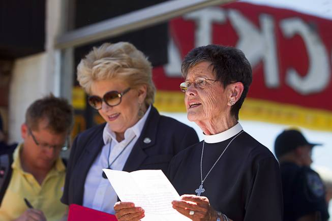 The Rev. Deacon Bonnie Polley gives an invocation during the grand reopening of The Atomic on East Fremont Street Wednesday, June 20, 2013. Las Vegas Mayor Carolyn Goodman listens at left. The bar was originally built in 1945 as Virginia's Cafe but was renamed Atomic Liquors in 1952 when patrons used to go to the roof to watch the nuclear blasts from the Atomic Test Site.