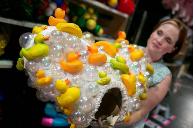 "Gillian Austin, wardrobe supervisor for the new ""Priscilla Queen of the Desert"" show, holds up an intricate ""Rubber Duckie"" head-dress used in the show, as seen Thursday, June 20, 2013."