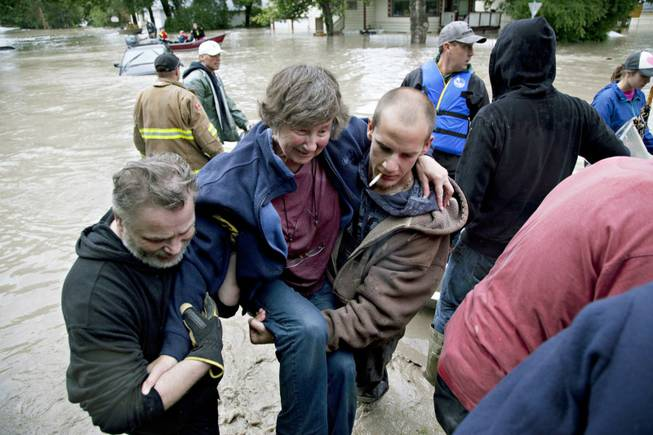 A woman is rescued from the flood waters in High River, Alberta on Thursday, June 20, 2013 after the Highwood River overflowed its banks.