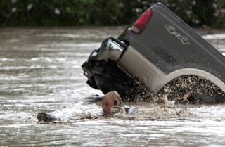 Kevan Yaets swims after his cat Momo to safety as the flood waters sweep him downstream and submerge his truck in High River, Alberta on Thursday, June 20, 2013 after the Highwood River overflowed its banks. Hundreds of people have been evacuated with volunteers and emergency crews helping to aid stranded residents.