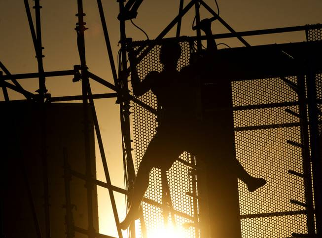 "An athlete is silhouetted against the setting sun while attempting a test run during Season 5 of ""American Ninja Warrior"" on Saturday, June 22, 2013, near the Strip."