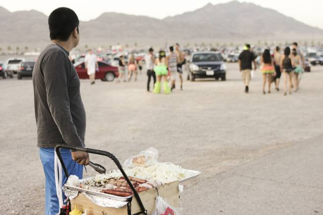 A food vendor selling hot dogs in the parking lot watches festival-goers leave at the end of day two of the Electric Daisy Carnival festival at the Las Vegas Motor Speedway, Sunday morning, June 23, 2013.