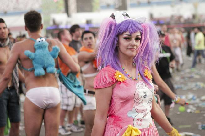 "A man wearing a Cookie Monster backpack is seen in the background as a woman in a ""My Little Pony""-themed outfit walks by during Headhunterz's set at the Electric Daisy Carnival at Las Vegas Motor Speedway on Sunday, June 23, 2013."
