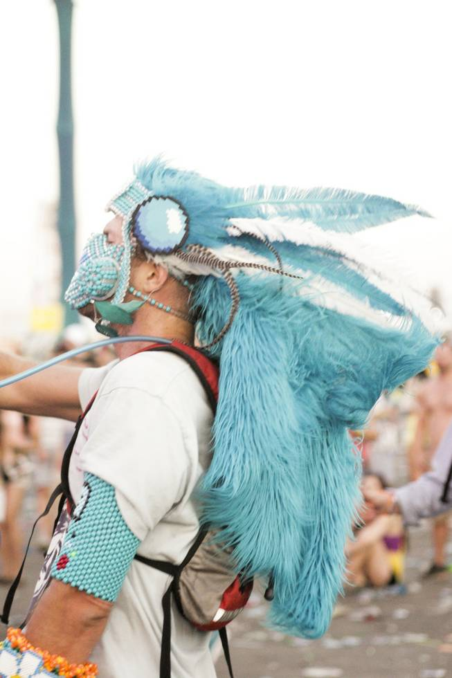 A festival goer wears a large blue feathered head dress at the Electric Daisy Carnival Festival, EDC, at the Las Vegas Motor Speedway, Sunday morning, June 23, 2013.