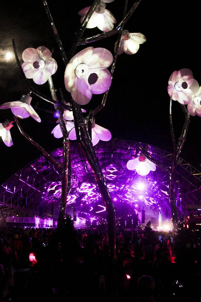 The full moon is seen behind an art installation at the Electric Daisy Carnival Festival, EDC, at the Las Vegas Motor Speedway, Sunday morning, June 23, 2013.