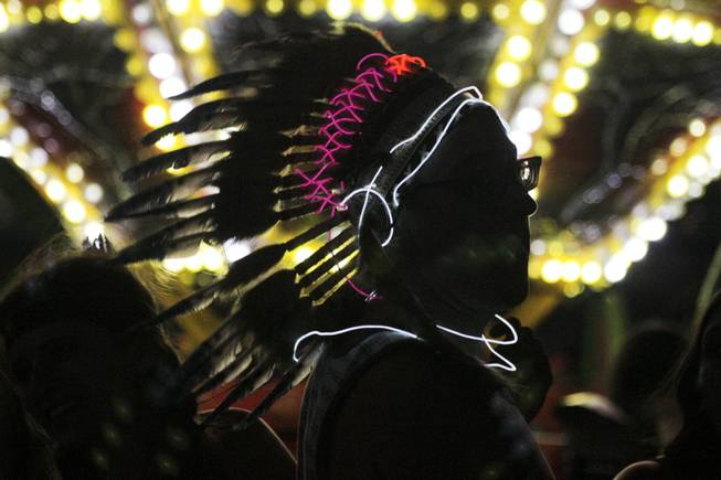 A festival goer wearing a lit up feather headdress waits in line for a carnival ride at the Electric Daisy Carnival Festival, EDC, at the Las Vegas Motor Speedway, Sunday morning, June 23, 2013.