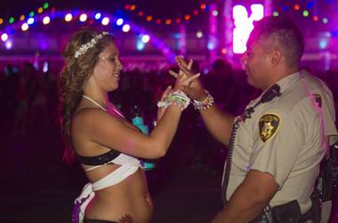 Sky Corona, 20 of La Habra, Calif. gives a bracelet to Metro Police Officer Pablo Torres during the third day of the Electric Daisy Carnival at the Las Vegas Motor Speedway early Monday morning, June 24, 2013.