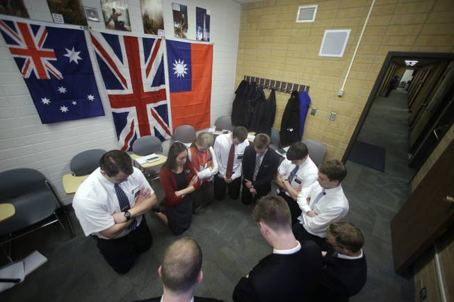 In this Jan. 8, 2013, file photo, Mormon missionaries pray before the start of a class in Mandarin Chinese language at the Missionary Training Center, in Provo, Utah.  Mormon missionaries will soon spend less time knocking on doors and more time chatting online with potential converts.