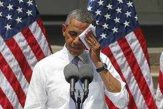 President Barack Obama wipes his face as he speaks about climate change, Tuesday, June 25, 2013, at Georgetown University in Washington. The president is proposing sweeping steps to limit heat-trapping pollution from coal-fired power plants and to boost renewable energy production on federal property, resorting to his executive powers to tackle climate change and sidestepping the partisan gridlock in Congress.