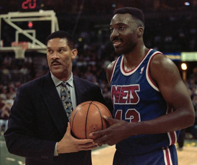 Armen Gilliam (right) accepts a commemorative ball from New Jersey Nets coach Butch Beard after Gilliam scored his 10,000th career NBA point on Feb. 21, 1996, in Milwaukee.