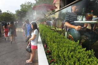 Passersby take advantage of the misters at the Candy Factory to cool off on the Strip Saturday, June 29, 2013.