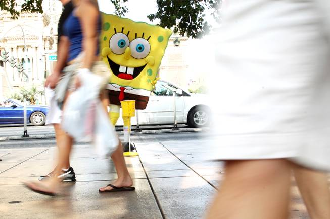 A man wearing a SpongeBob outfit waits in the shade ...