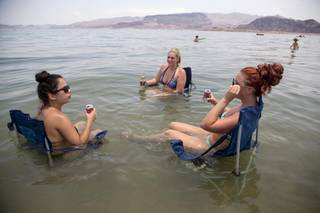 From left, Subrina Madrid, Sarah Hudak, Jennifer, Shackelford, all of North Las Vegas, sit in the shallow waters along Boulder Beach at Lake Mead, Saturday, June 29, 2013. The three planned to spend the day at the lake to escape the heat in Las Vegas, where Saturday's daytime high was expected to reach 117 degrees.