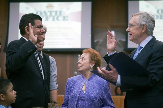 Councilman Isaac Barron, left, is sworn in by Senate Majority Leader Harry Reid (D-NV) during an oath of office ceremony at North Las Vegas City Hall Monday, July 1, 2013. Barron is the first Hispanic to serve on the North Las Vegas City Council. Barron's aunt Socorro Molina is at center.
