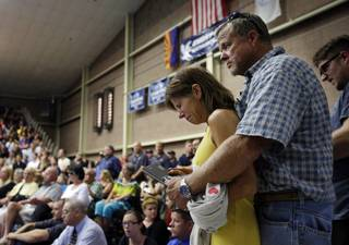 Marsha McKee and Stanley Nesheim react during a memorial service for 19 firefighters of the Granite Mountain Hotshot Crew, Monday, July 1, 2013, in Prescott, Ariz. McKee is the mother of one of the Hotshots who were killed by an out-of-control blaze near Yarnell, Ariz. on Sunday.