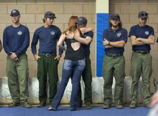 A woman hugs a firefighter before the start of a memorial service, Monday, July 1, 2013 in Prescott, Ariz. The service was held for the 19 Granite Mountain Hotshot Crew firefighters who were killed Sunday, when an out-of-control blaze overtook the elite group. (AP Photo/Julie Jacobson)