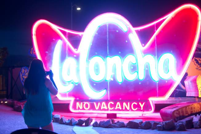 "A woman takes a photo of the ""La Concha"" sign during a night tour at The Neon Museum, Monday, July 1, 2013."