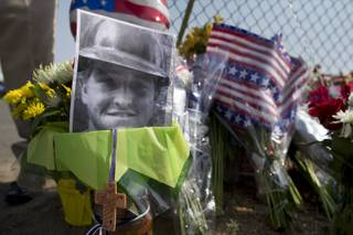 A photo of one of the 19 Granite Mountain Hot Shot crew members who was killed fighting a wild land fire near Yarnell, Ariz. on Sunday, sits at a makeshift memorial outside the crew's fire station, Monday, July 1, 2013 in Prescott, Ariz. An out-of-control blaze overtook the elite group of firefighters trained to battle the fiercest wildfires, killing 19 members as they tried to protect themselves from the flames under fire-resistant shields.
