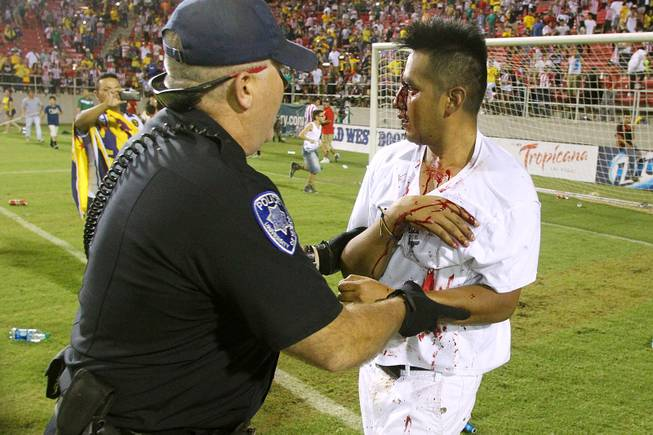 A bloodied soccer fan is led off the field by a UNLV policeman after El Super Clasico soccer game Wednesday, July 3, 2013 at Sam Boyd Stadium.