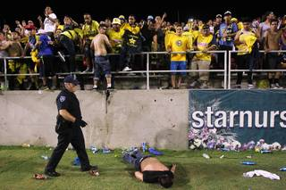 A Chivas fan lies motionless on the field after being beaten nearly unconscious by Club America fans after El Super Clasico soccer game Wednesday, July 3, 2013 at Sam Boyd Stadium.