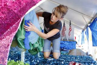 Volunteer Elizabeth Engle puts the finishing touches on floats for the Summerlin Council Patriotic Parade on Wednesday, July 3, 2013.