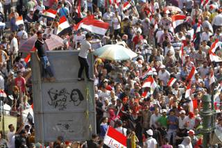 Opponents of Egypt's Islamist President Mohammed Morsi shout slogans during a protest in Tahrir Square in Cairo, Egypt, Wednesday, July 3, 2013. Arabic reads,