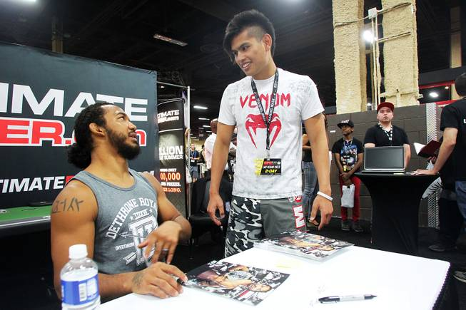Jose Bernardo gets a chance to talk to UFC fighter Benson Henderson at the Ultimate Poker booth during the UFC Fan Fest at Mandalay Bay Friday, July 5, 2013.