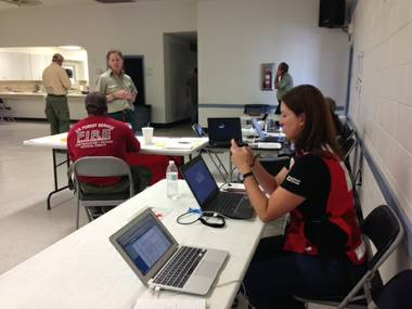 Jennifer Ramieh, a spokeswoman for the Southern Nevada Chapter of the American Red Cross, checks a Twitter account as a wildfire burns on Mount Charleston on July 5, 2013.