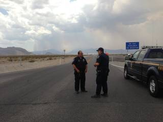 Smoke from a wildfire rises from Mount Charleston as Nevada Highway Patrol Troopers Roger Fickle, left, and Brian Drohn man a checkpoint along State Route 157 near U.S. 95.