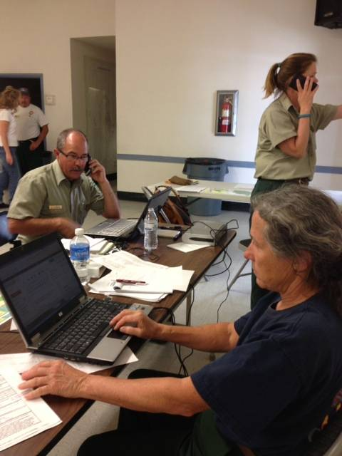 U.S. Forest Service spokeswoman Betsy Ballard (on laptop), Forest Service spokesman Jay Nichols (seated on phone) and Park Service Ranger Genny Wilson of Carson City (standing on phone) monitor progress of the Carpenter 1 fire on Mount Charleston on July 5, 2013.