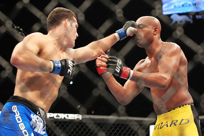 Chris Weidman tags Anderson Silva with a left during their middleweight title fight at UFC 162 Saturday, July 6, 2013 at the MGM Grand Garden Arena. Weidman upset Silva with a second round knockout, taking the belt Silva has held since 2006.