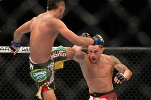 Frankie Edgar blocks a kick from Charles Oliveira during their fight at UFC 162 Saturday, July 6, 2013 at the MGM Grand Garden Arena. Edgar won by unanimous decision.