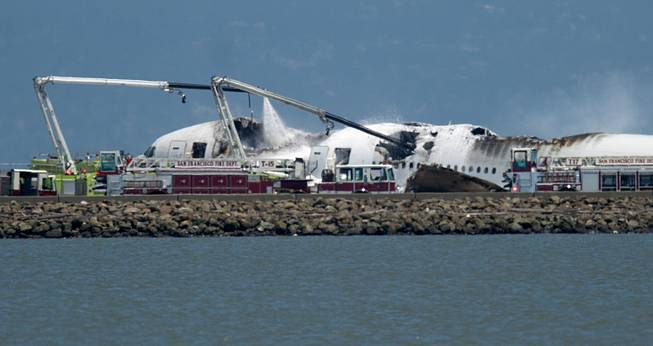 A firetruck sprays water on a Boeing 777 after Asiana Flight 214 crashed at San Francisco International Airport on Saturday, July 6, 2013, in San Francisco.