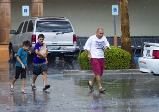 A family heads to their car after grocery shopping during a rainstorm in Henderson Sunday, July 7, 2013. (No names provided).