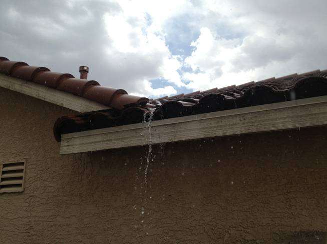 Rain runs off the roof of a Henderson home, Sunday, July 7, 2013.