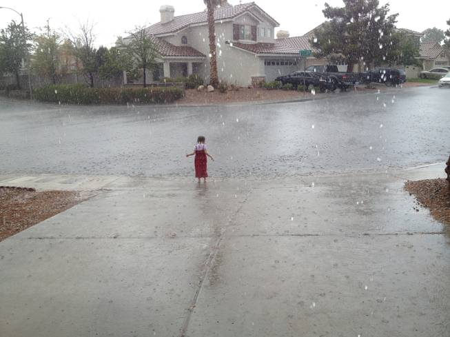A girl plays in the rain in Green Valley, Sunday, July 7, 2013.